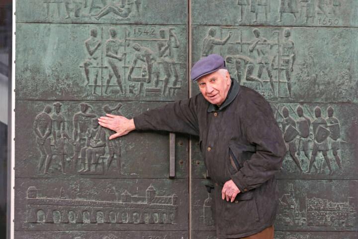 Der Künstler der Bronze-Reliefs, Gerd Jäger (90), 2012 vor seinem noch  unrestaurierten Werk von 1969.