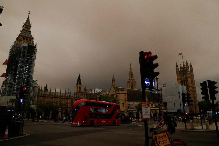 """Der Palace of Westminster ist am 16.10.2017 in London vor einem matt-orangefarbenen Himmel zu sehen. Aufgrund von """"Ophelia"""" hat er eine ungewöhnliche Färbung angenommen."""