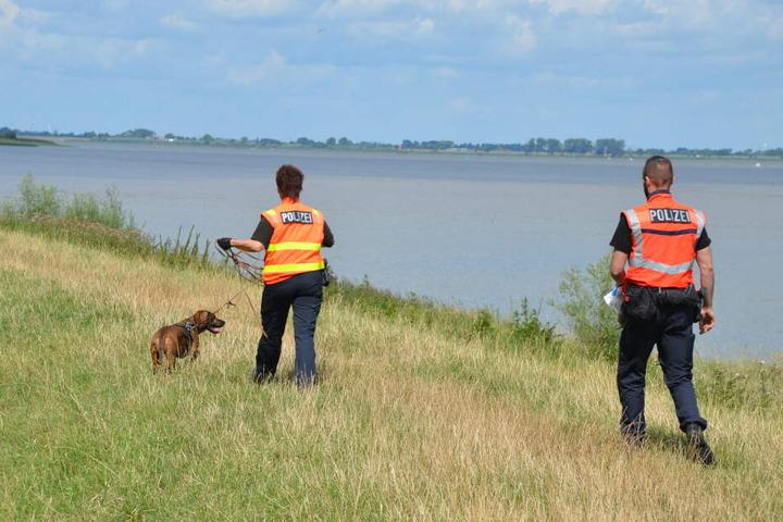 Beamte suchen das Ufer der Elbe nach Spuren ab.