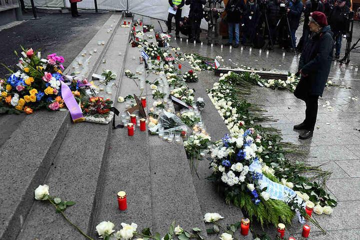 Passanten gedenken ein Jahr danach mit Blumen und Kerzen den Opfern.