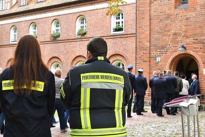 Zwei Feuerwehrleute aus Werder stehen vor dem Kloster Lehnin, wo die Trauernden sich versammelten.