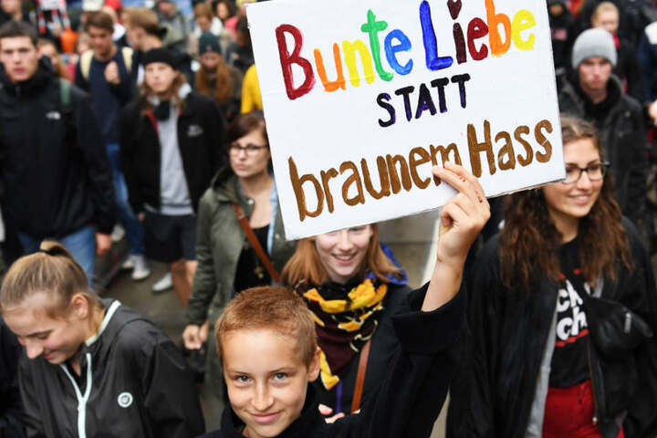 """Ein junger Teilnehmer des Demonstrationszuges hält ein Schild mit der Aufschrift """"Bunte Liebe statt braunem Hass""""."""