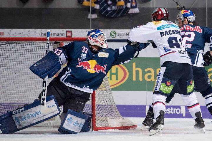 Sean Backman (r) von Berlin kämpft mit Torwart Danny Aus Den Birken von München um den Puck.