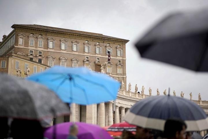 Menschen stehen unter Regenschirmen auf dem Petersplatz, um den Segen von Papst Franziskus zu empfangen.