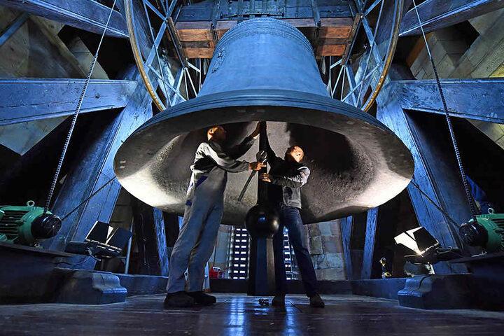 (v.l.) Glockenwart Uwe Kramer und Mechaniker Christian Garamvölgy arbeiten unter der meterhohen Glocke.