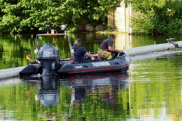 Feuerwehrleute suchen vom Boot aus die Uferzonen nach dem Vermissten ab.