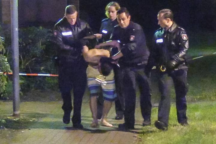 Polizisten führen einen jungen Mann in Badehose ab.