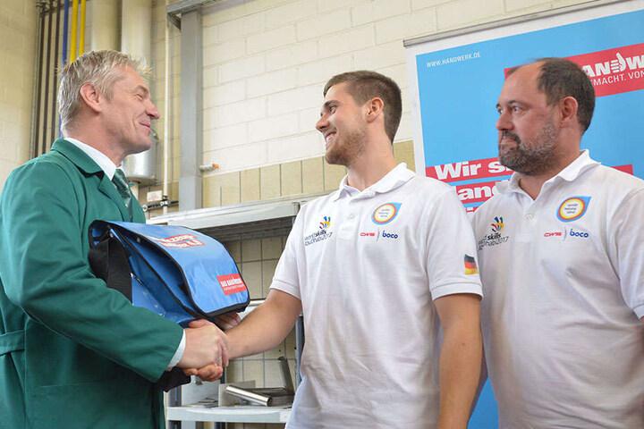 Ausbilder Thomas Günther und Trainer André Schnabel übergeben Lukas die Werkzeugtasche.