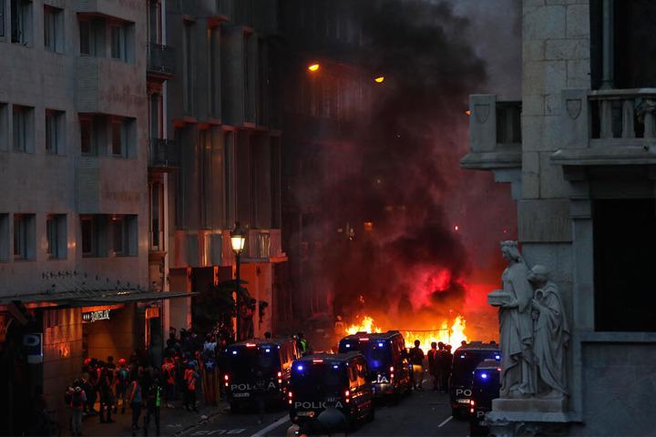 Brennende Straßenbarrikaden versperren in Barcelona die Straßen.