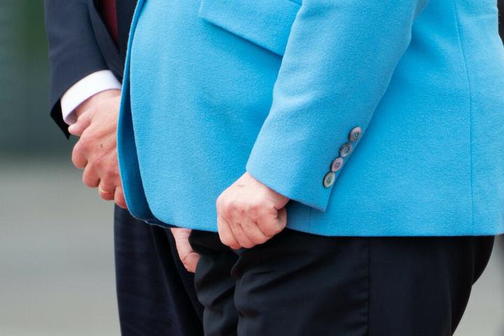 Angela Merkel presst beim Empfang die Hände zusammen.
