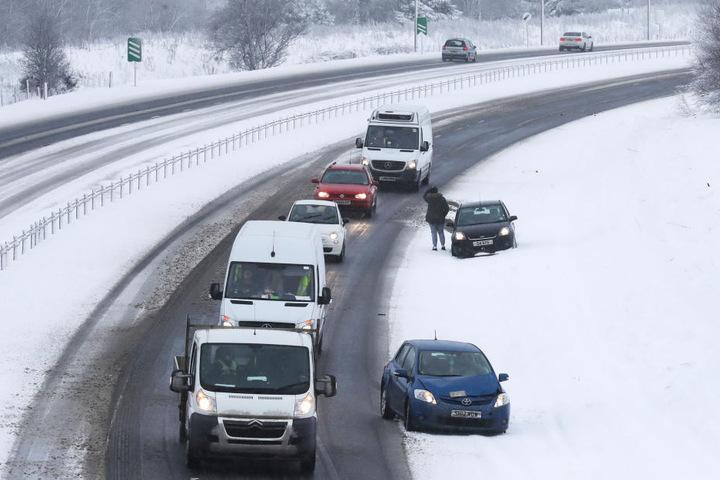 Autos stehen in Greenloaning (Großbritannien) auf der A9 am Straßenrand.