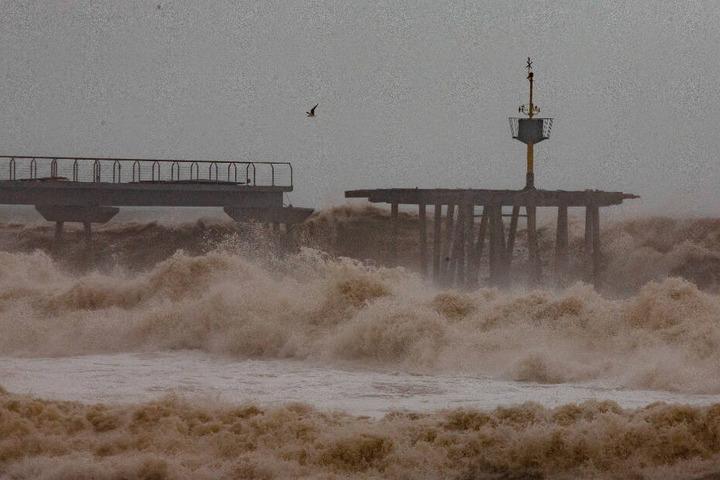 Wellen treffen eine teilweise beschädigte Brücke während eines Sturms am Strand von Badalona.