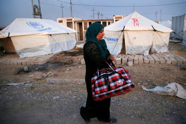 Eine syrische Frau, die durch die türkische Militäroperation im Nordosten Syriens vertrieben wurde, läuft mit einer Tasche in der Hand durch das Lager Bardarash, nördlich von Mosul. Vor der türkischen Militäroffensive sind nach Angaben der UN-Organisation