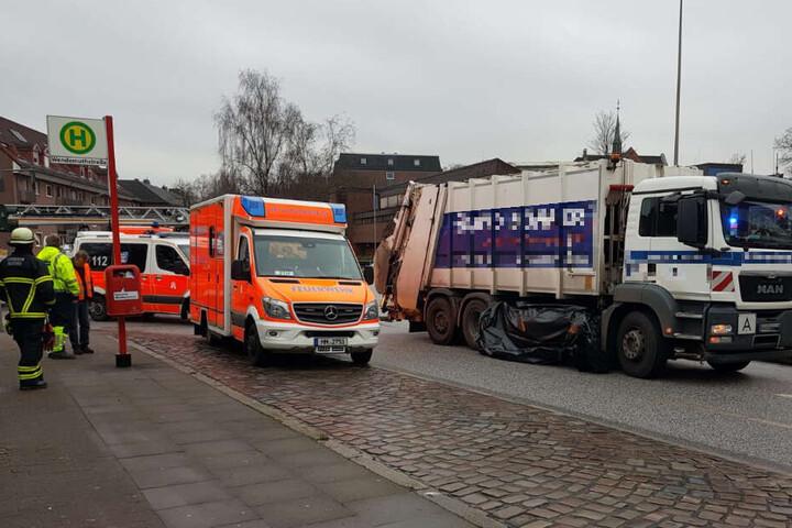Helfer haben um den Müllwagen eine Plane als Sichtschutz gezogen.