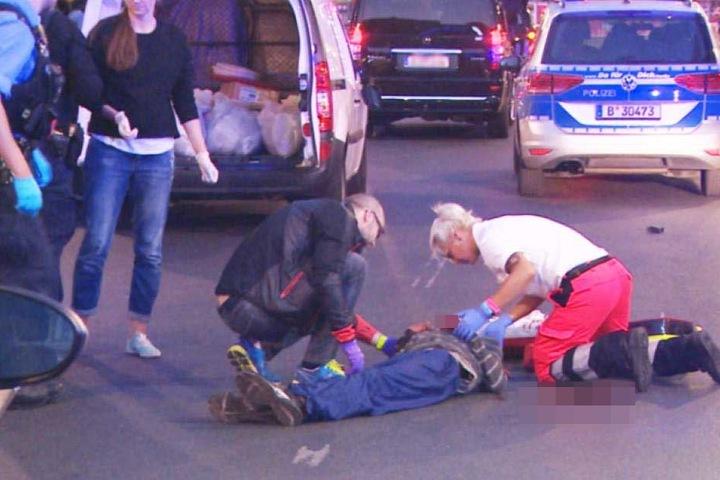 Sanitäter kümmern sich auf der Straße um den verletzten Mann.