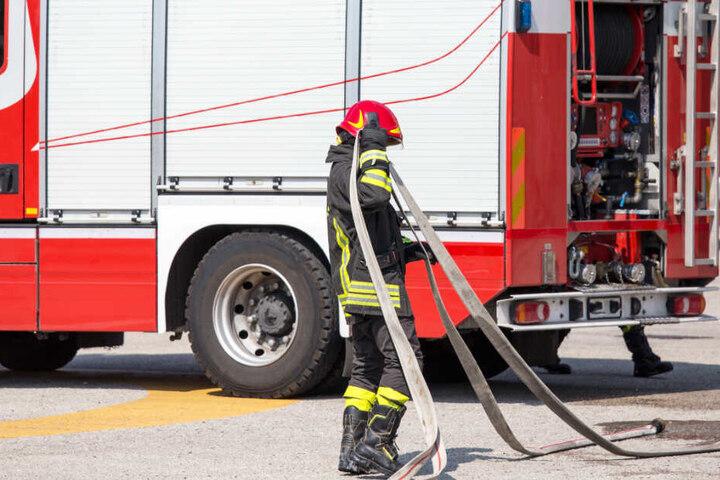 Ein Feuerwehrmitglied rollt nach dem Einsatz einen Schlauch auf. (Symbolbild)