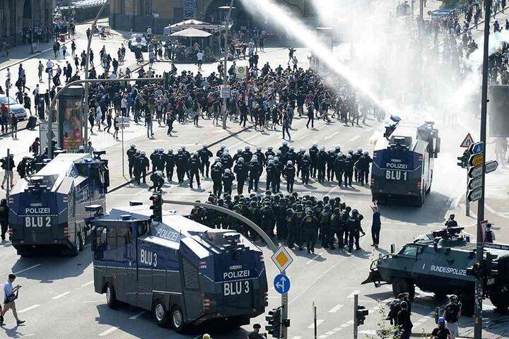 Nahe den Landungsbrücken setzen die Polizisten Wasserwerfer gegen Demonstranten ein.