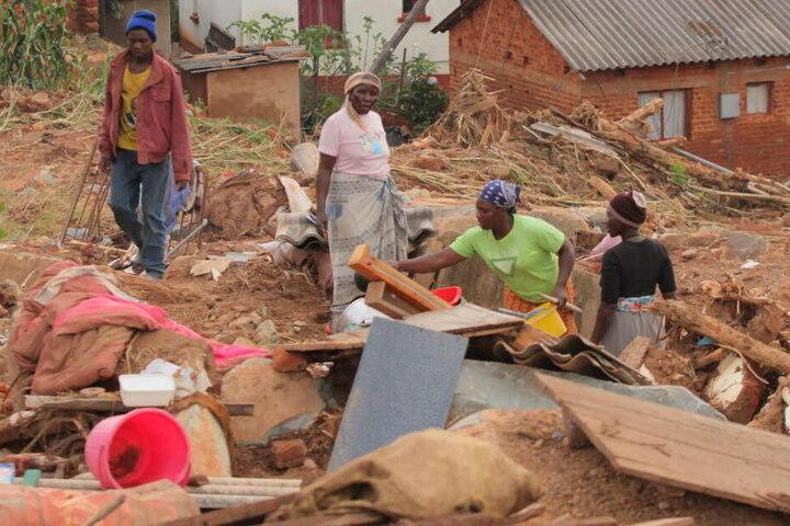 Bewohner eines Dorfes in Simbabwe suchen nach nutzbaren Gegenständen, nachdem der Wirbelsturm Idai ihr Dorf beschädigt hat.