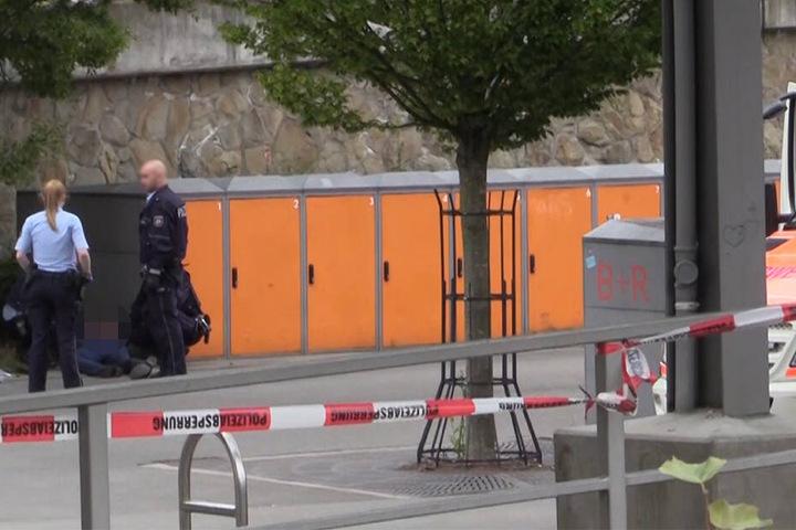 Polizisten stehen am Stadtbahnhof neben dem festgenommenen Tatverdächtigen, der am Boden liegt.