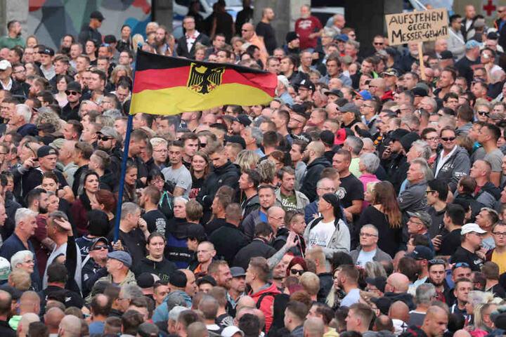 Rechte Demonstranten stehen vor dem Karl-Marx-Monument.