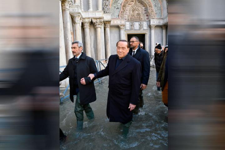 Silvio Berlusconi (M, 81), ehemaliger Ministerpräsident von Italien und Forza Italia-Parteichef, geht in Gummistiefeln bei Hochwasser über den Markusplatz.