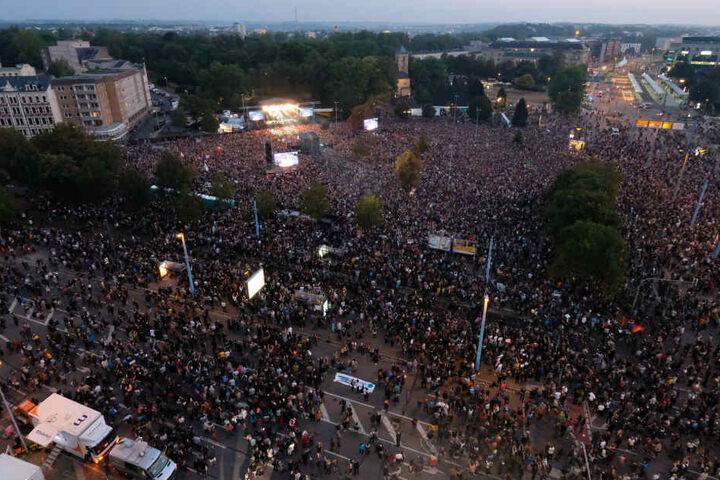 Zuschauer stehen während des Konzerts unter dem Motto «#wirsindmehr» auf dem Parkplatz vor der Johanniskirche.