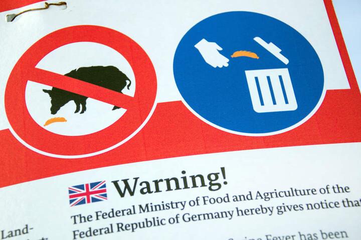 Eine Tafel informiert in verschiedenen Sprachen über Maßnahmen gegen die Ausbreitung der Schweinepest.