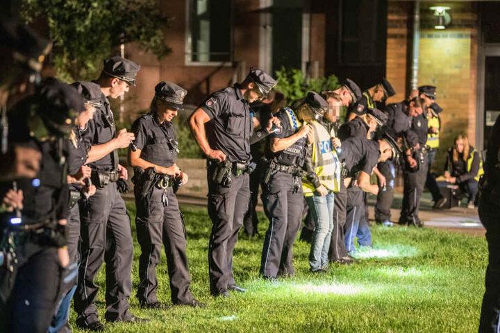 Beamte der Polizei suchen die Wiese vor dem Restaurant nach Spuren ab.