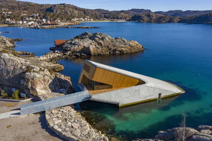 Das Gebäude ragt diagonal aus dem Wasser.