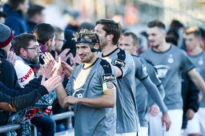 """""""Maskenmann"""" Toni Wachsmuth klatscht nach der Partie mit den Zwickauer Fans ab."""