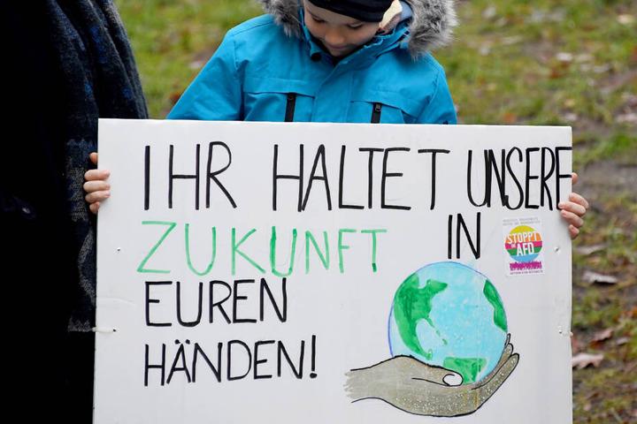 """Schleswig-Holstein, Kiel: Mit einem Schild mit der Aufschrift """"Ihr haltet unsere Zukunft in den Händen"""" steht ein Schüler bei einem Demonstrationszug."""