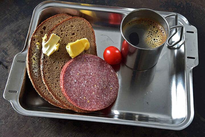 Caro-Kaffee, Brot, Margarine, Wurst und eine Tomate, serviert mit Plastebesteck, so sieht Essen im Knast aus.