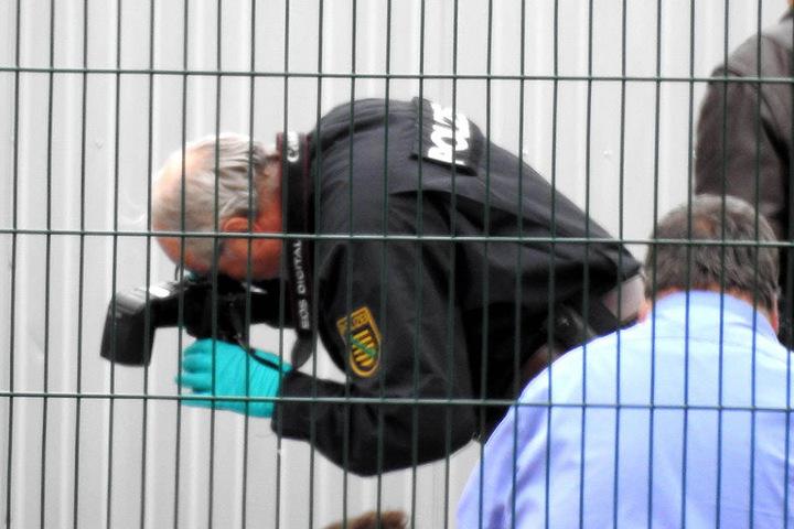Ein Kriminaltechniker fotografiert sichergestellte Schuhe und Bekleidung des Verdächtigen.