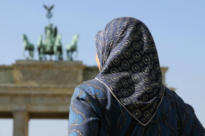 Eine Muslima mit Kopftuch vor dem Brandenburger Tor in Berlin.