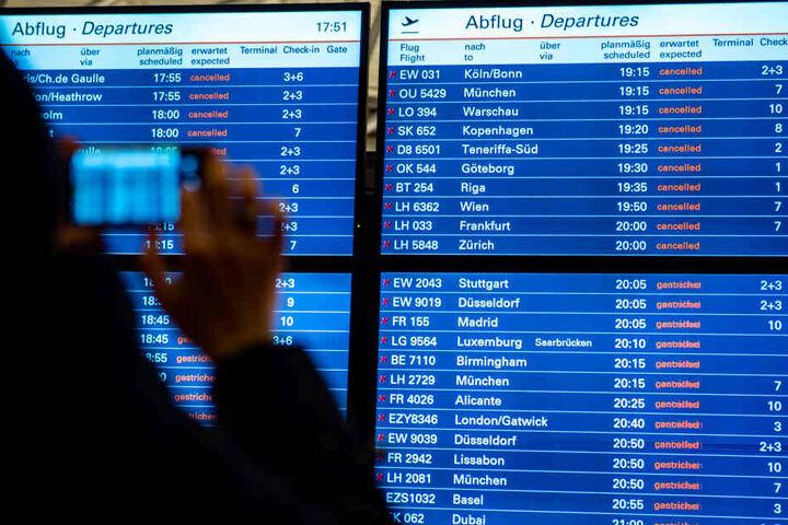 Februar 2019: Ein Fluggast fotografiert mit seinem Smartphone die Anzeigetafel im Hamburger Flughafen.