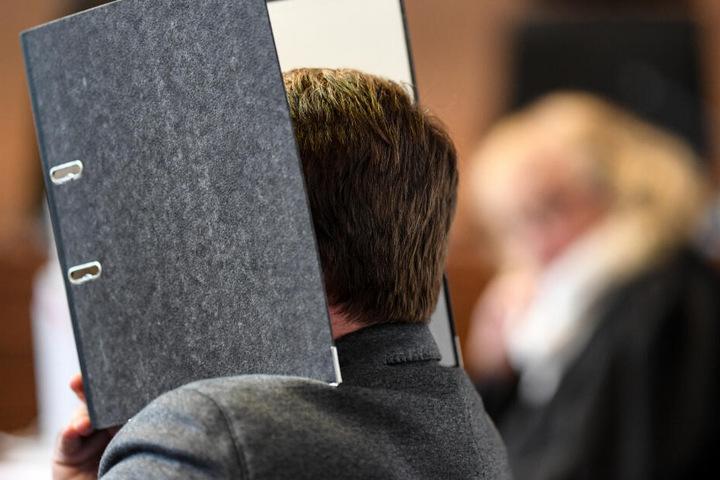 Der Angeklagte hält beim Prozess im Mai 2015 einen Aktenordner vor sein Gesicht.