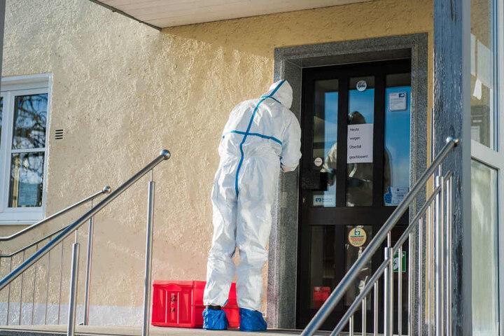 Ein Mann der Spurensicherung sichert Beweise an der Tür der Bank.