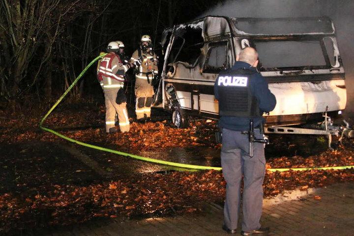 Polizei und Feuerwehr begutachten den zerstörten Wohnwagen.