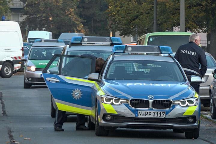 Polizeibeamte stehen an einem Streifenfahrzeug im Nürnberger Stadtteil Werderau.