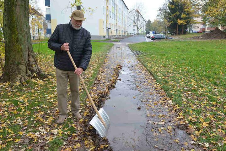 Claus Modaleck (77) schob gestern notdürftig den Schlamm beiseite, den der nächtliche Regen auf den Weg gespült hatte.