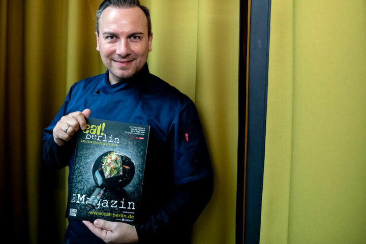 """Tim Raue, Koch, hält bei einem Pressetermin anlässlich der Vorstellung des Programms des Feinschmeckerfestivals """"eat! Berlin"""" das Festivalmagazin."""