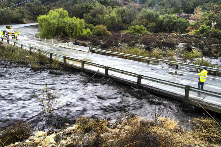 Ein Mitarbeiter von Orange County nimmt ein Video von dem von Asche und Schutt der Waldbrände geschwärzten Sturzflut auf.