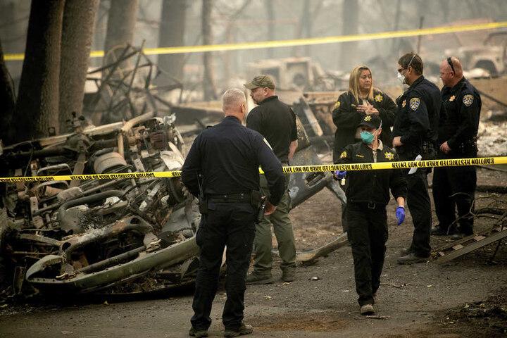 """Beamte bergen die menschlichen Überreste eines Opfers des """"Camp""""-Feuers aus einem umgekippten Auto."""