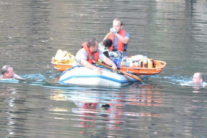 Rettungskräfte bringen den Mann zum Abtransport an eine geeignetere Stelle. Zur Absicherung schwimmen zwei Feuerwehrmänner neben dem Boot her.