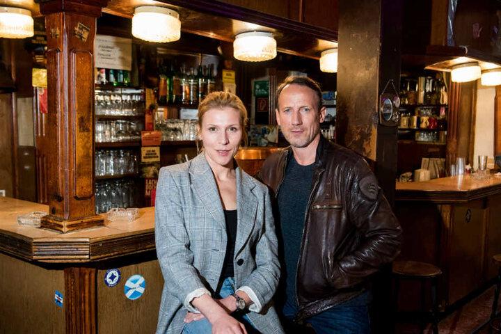 Das Ermittler-Duo steht in einer Kneipe vor einer Bar.