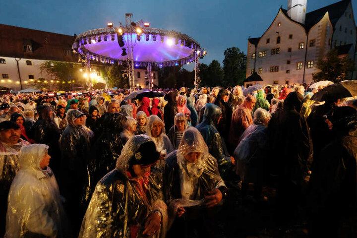 """Besucher der MDR-Open-Air-Show """"Die Schlager des Sommers"""" verlassen den Hof von Schloss Klaffenbach. Wegen eines heftigen Gewitters musste die Aufzeichnung unterbrochen werden."""
