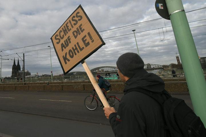 Ein Teilnehmer hält bei einer Demonstration von Umweltschützern «Kohle Stoppen - Klimaschutz jetzt» ein Schild hoch auf dem steht «Scheiss auf die Kohle!»