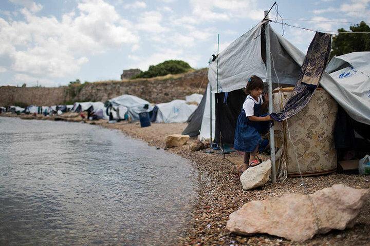 Ein Flüchtlingsmädchen aus Syrien geht am Strand von Chios (Griechenland) vor Zelten entlang. Die Zelte sind eine provisorische Unterkunft in der Nähe des Flüchtlingslagers Souda.