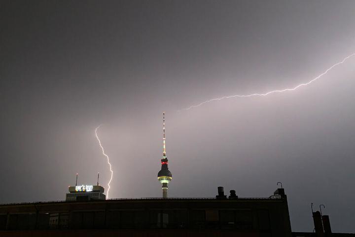 Blitze zucken während eines Gewitters über dem Fernsehturm.