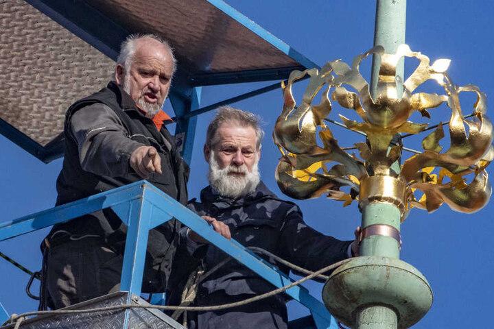 Zwei Arbeiter befestigten die goldene Krone auf dem Rathausdach.